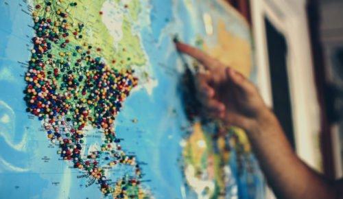 Världskarta USA i fokus med instuckna nålar och hand som pekar
