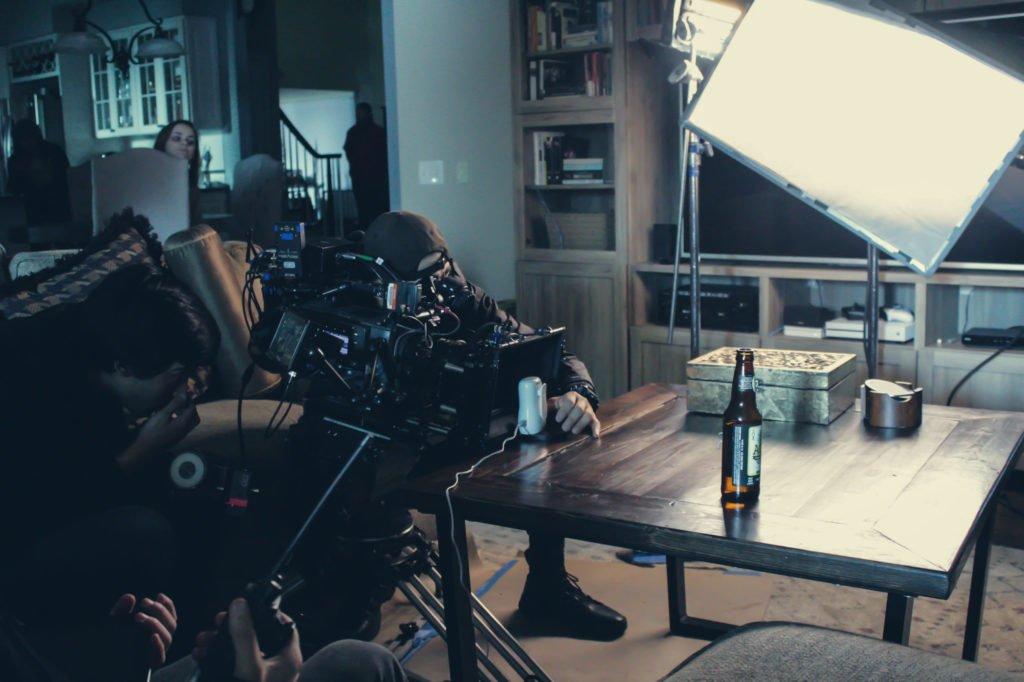 Fotografer filmar en glasflaska på vardagsrumsbord