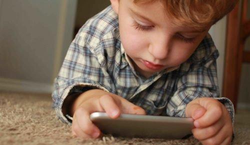 Pojke ligger på golvet och surfar på en mobiltelefon