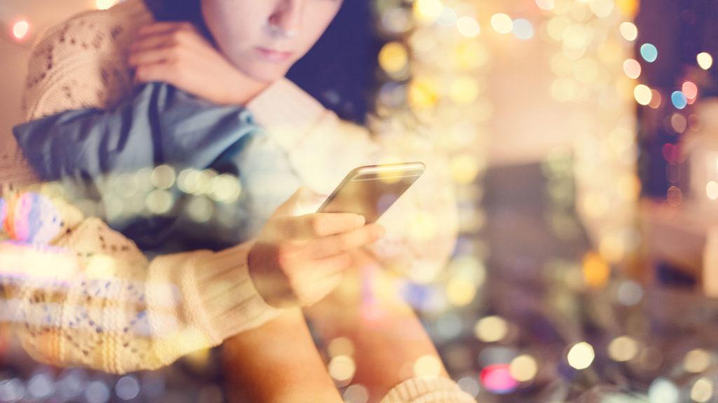 Flicka som sitter böjd över mobilen