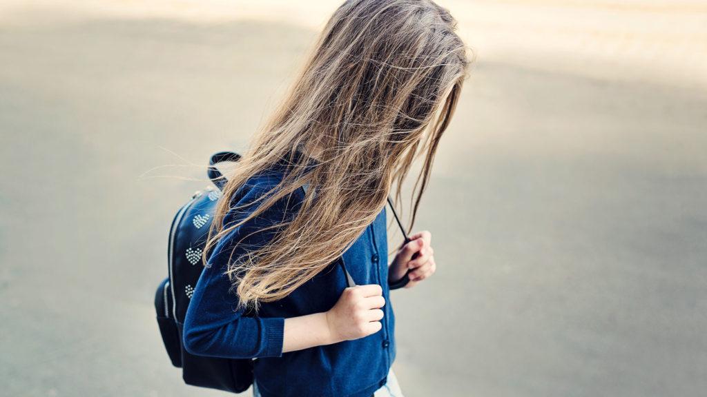 Flicka med långt hår som går med hängande huvud.