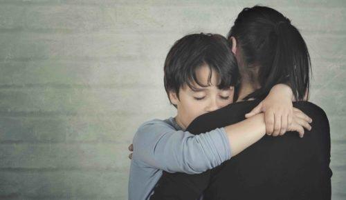 Mamma kramar om sin son. Nätmobbning. Internetkunskap