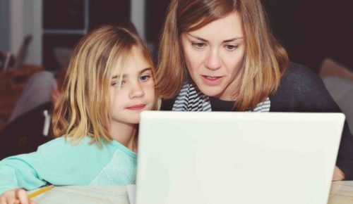 Mamma och dotter tittar tillsammans på en laptop