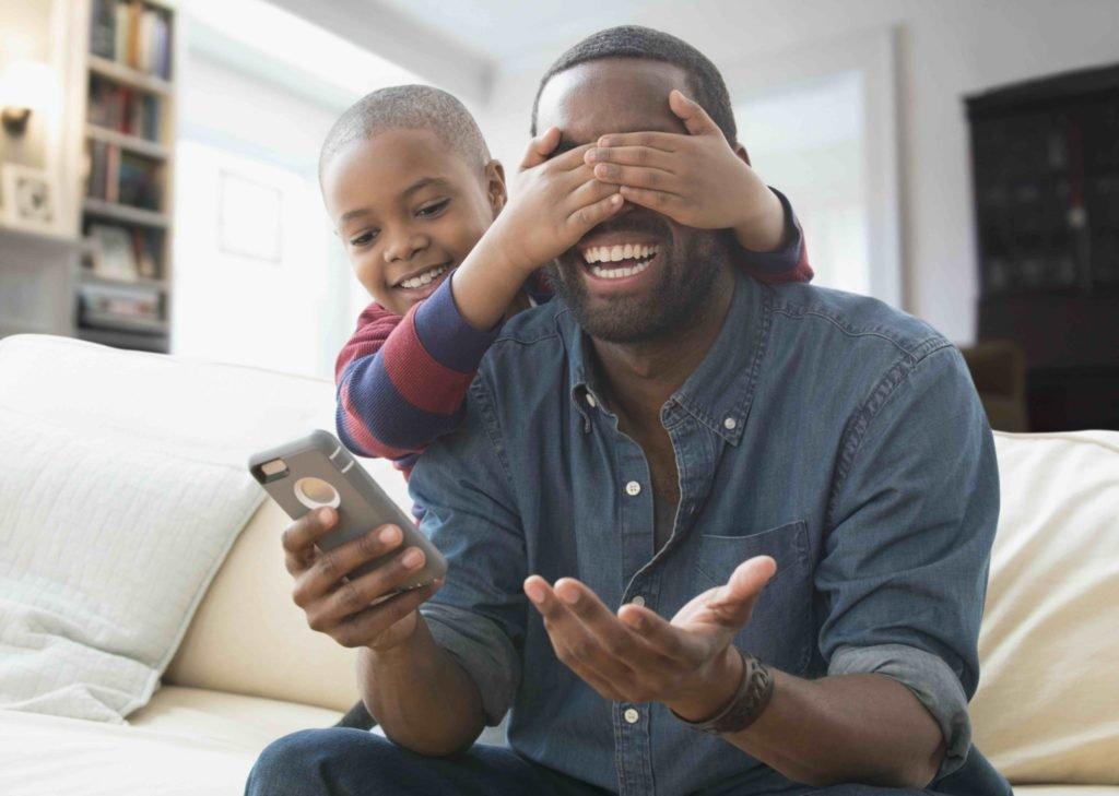 Pojke håller för ögonen på sin pappa som skrattar och håller mobiltelefon i handen.