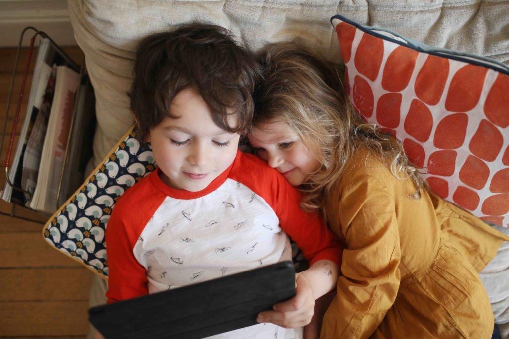 Två barn ligger i soffa och tittar på surfplatta