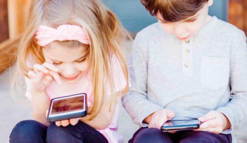 En pojke och en flicka sitter bredvid varandra och tittar ner i en varsin mobiltelefon