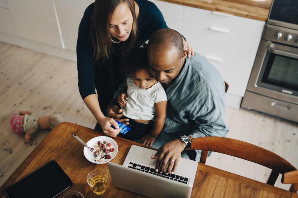 High angle view of parents with daughter shopping online on laptop at dining room