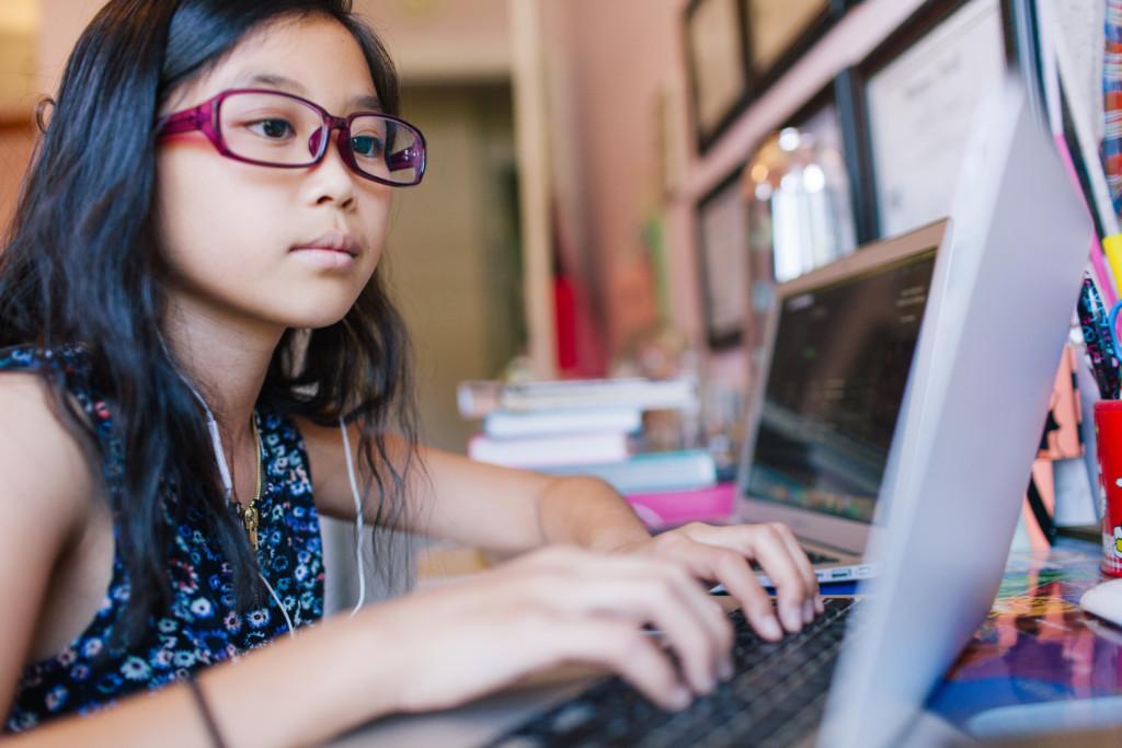 Flicka sitter framför en laptop och skriver på tangentbord. Internetkunskap