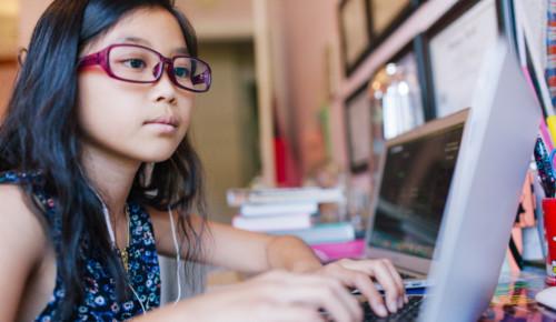 Flicka sitter framför en laptop