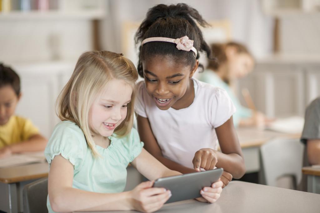 Två flickor tittar på en padda tillsammans och skrattar