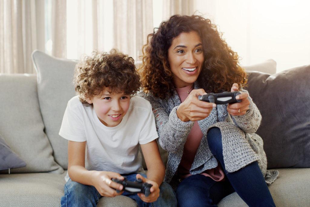 Kvinna och pojke spelar tv-spel i en soffa