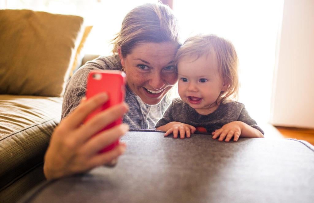 Kvinna och bebis tar en selfie med mobiltelefon.