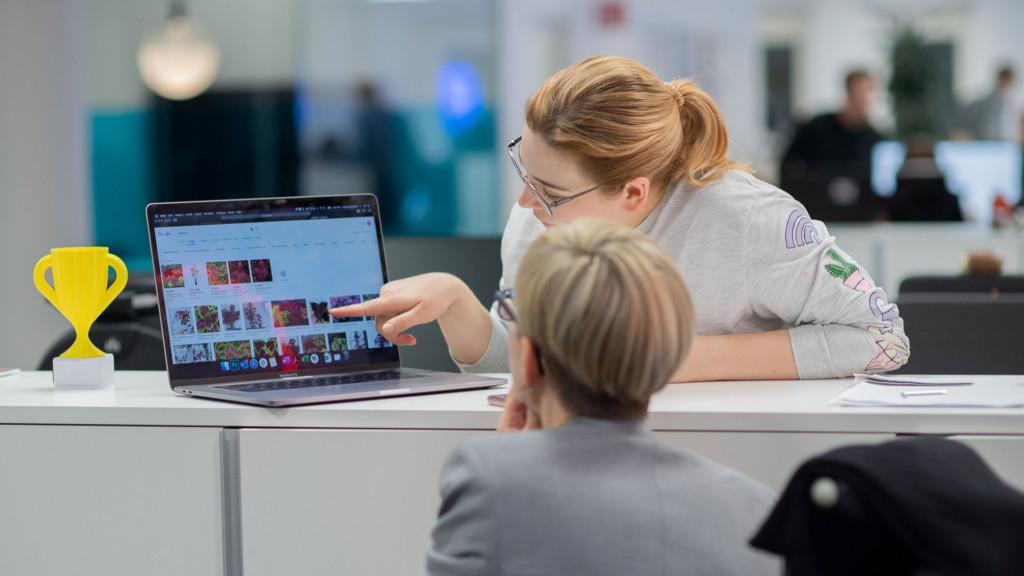 Två kvinnor som tittar på en dator i kontorsmiljö.