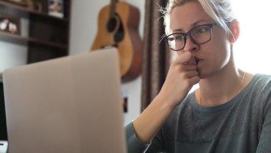 Bekymrad kvinna biter på naglarna framför en laptop