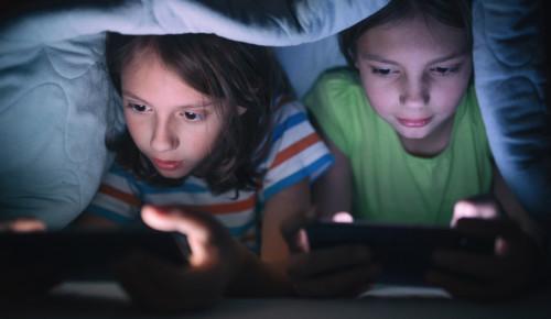 Två barn sitter under täcke och spelar på sina mobiler