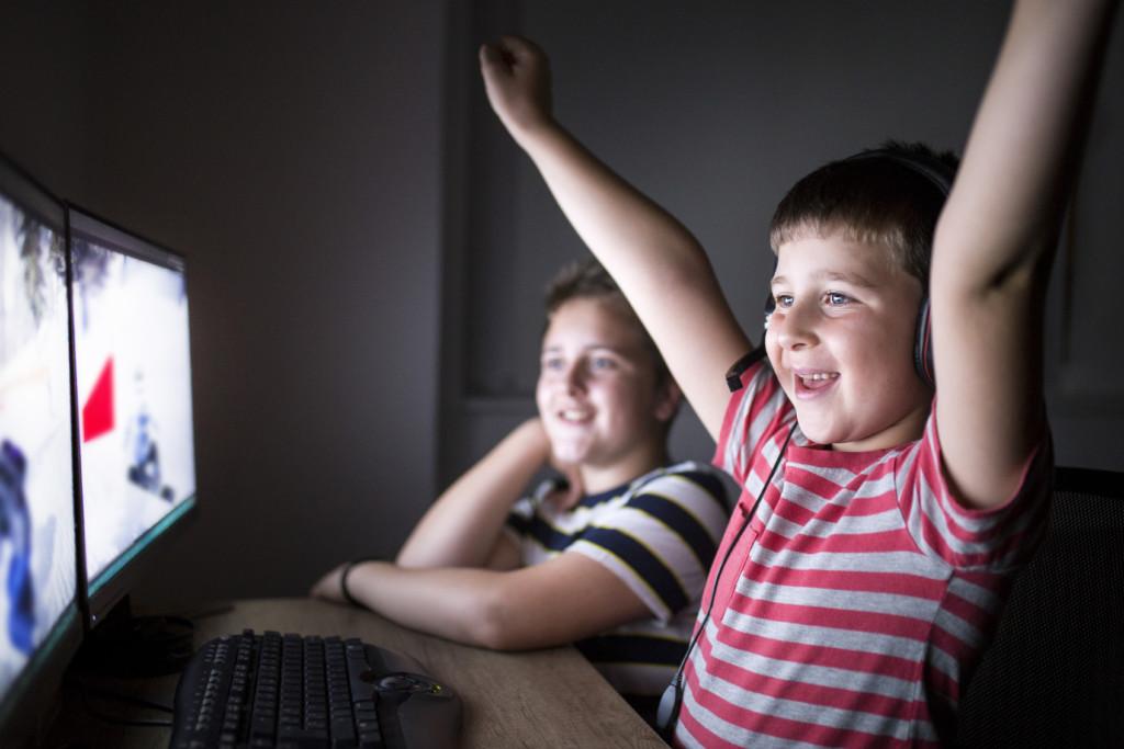 Två pojkar sitter och spelar online