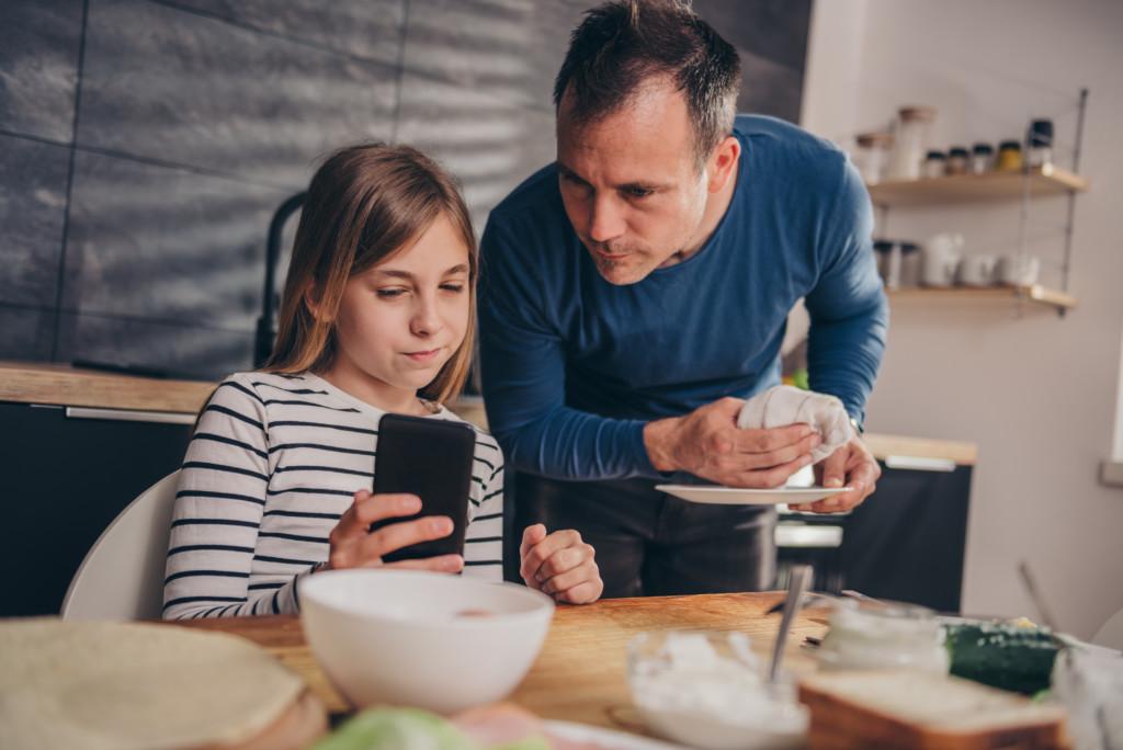 Flicka sitter vid köksbordet och visar sin pappa något i mobilen