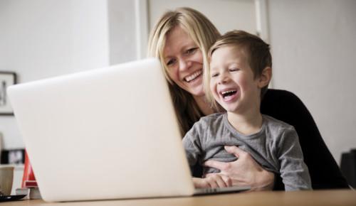 Glad mor och son sitter framför en laptop