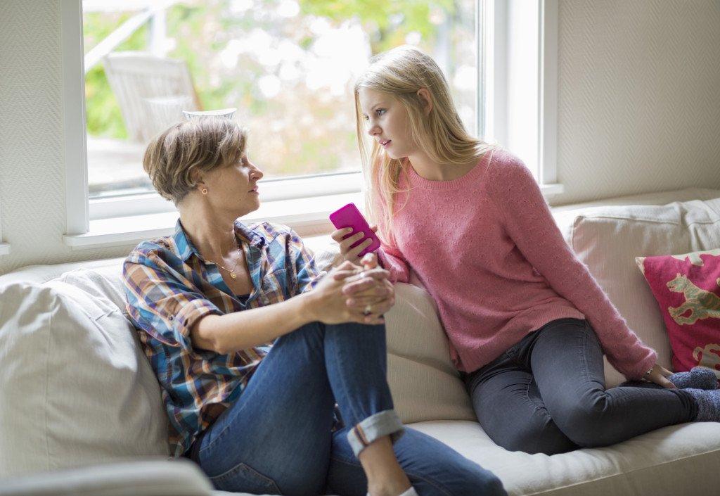 Förälder och barn talar med varandra i soffa