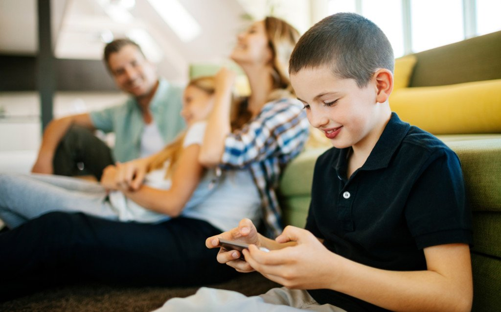 Barn sitter med sin familj och kollar på en mobiltelefon
