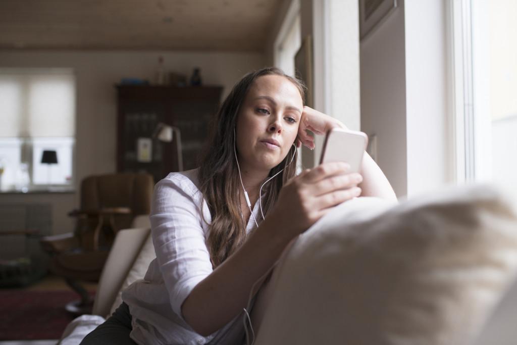 Kvinna som kollar på mobil i soffan.