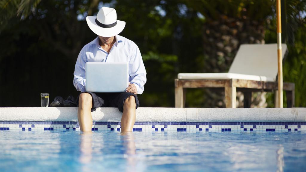 Man med hatt med dator och fötterna i poolen. Se Netflix utomlands