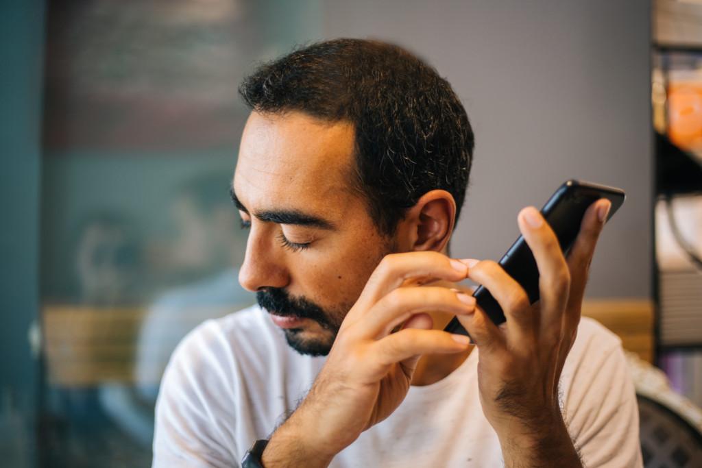 Man som håller i en mobiltelefon. Så funkar DNS