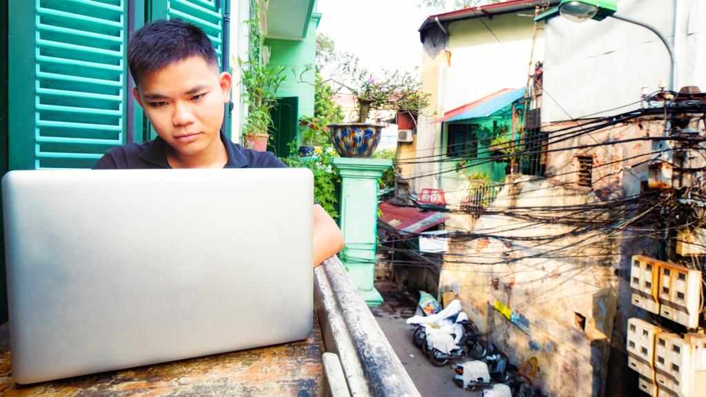 Kille från Asien som sitter i fönster och surfar på sin dator. internet mänsklig rättighet