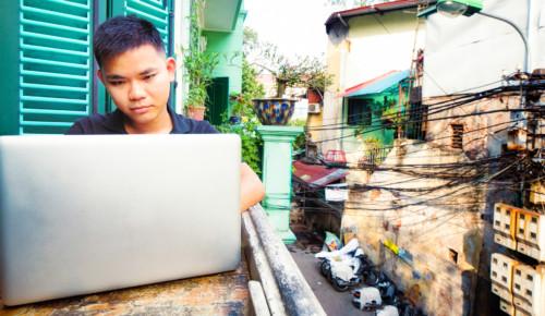 Kille från Asien som sitter i fönster och surfar på sin dator.