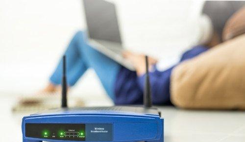 Närbild på router med kvinna som surfar i bakgrunden.