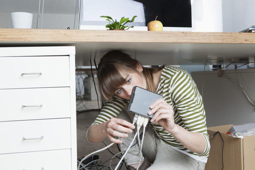 Kvinna undersöker nätverkssladd i router. Vad är internet. Internetkunskap