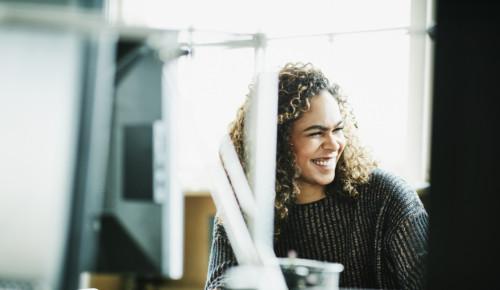 Glad kvinna framför dator på kontoret.