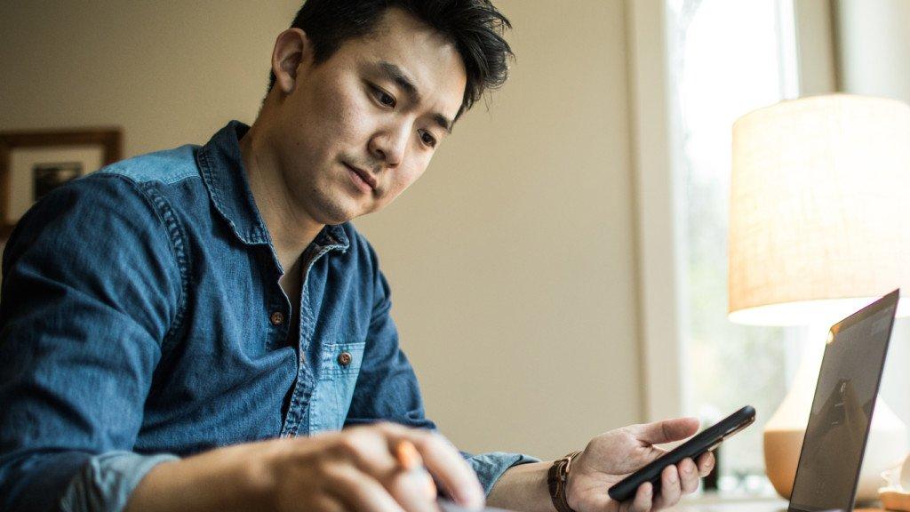 Bilden visar en man som arbetar med sin dator och mobiltelefon.